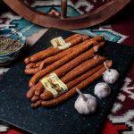 CABANOS OAIE: Produs fiert și dublu afumat cu membrană naturală comestibilă din carne de oaie (50%), porc și vită, aromatizat cu condimente naturale (piper, usturoi, cimbru, coriandru).