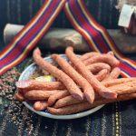 CABANOS ŢĂRĂNESC: Produs fiert și dublu afumat cu membrană naturală comestibilă din carne porc și vită, aromatizat cu condimente naturale.