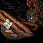 CÂRNAŢI CU VIN ŞI BUSUIOC: Produs fiert și afumat cu membrană naturală comestibilă, cu carne de porc, aromatizat cu condimente naturale și vin.