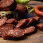 CÂRNAŢI PICANŢI SASCA: Produs fiert și afumat cu membrană naturală comestibilă, cu carne de porc, aromatizat cu condimente naturale și paprika.