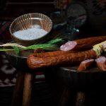 CÂRNAŢI ŢĂRĂNEȘTI: Produs fiert și afumat cu membrană naturală comestibilă, cu carne de porc, aromatizat cu condimente naturale.