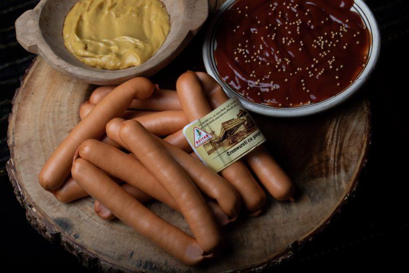CREMWURŞTI DE PUI: Produs fiert și afumat, membrană comestibilă, cu piept de pui și condimente naturale.